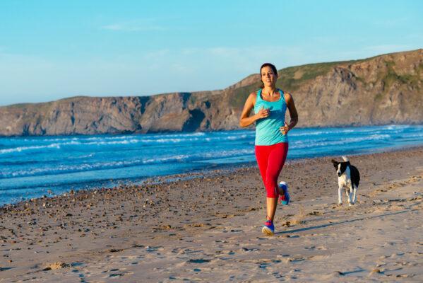 Frau beim Joggen mit Hund am Strand